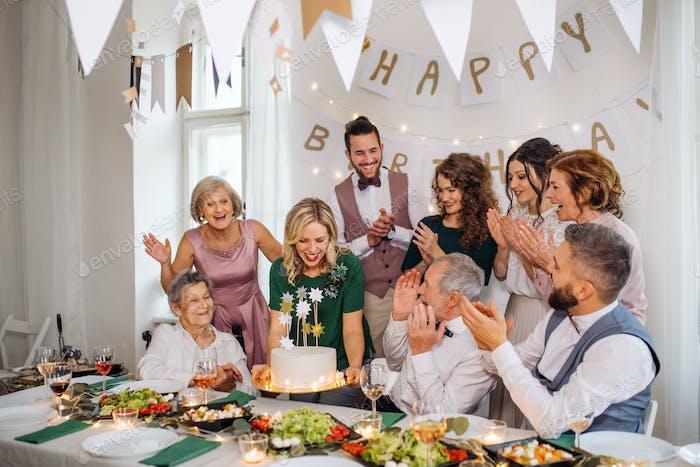 Ein Senior Mann mit Mehrgeneration Familie feiert Geburtstag auf Indoor-Party.