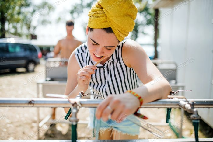 Young woman at summer festival, brushing teeth by basins