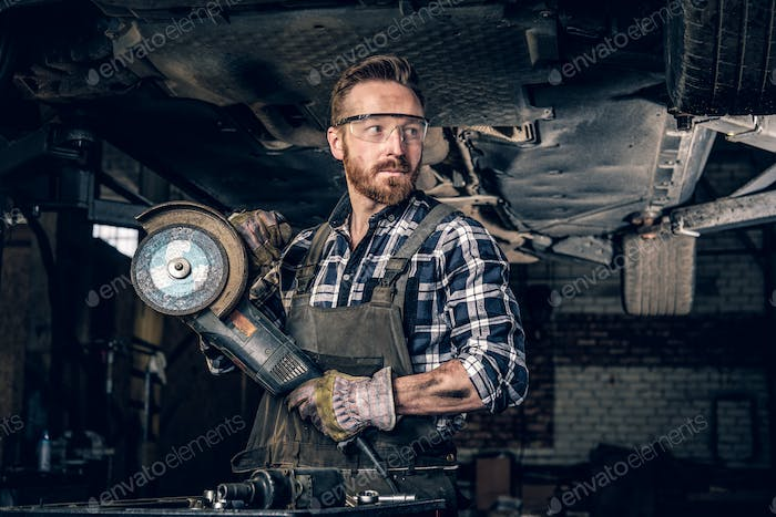 Mechanic in protective googles holds angle grinder.