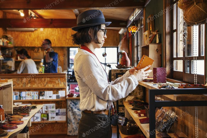 Japanese woman wearing hat and glasses browsing merchandise in a leather shop.