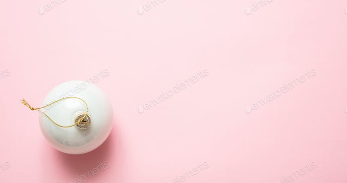 Xmas bauble white color against pink background, high angle