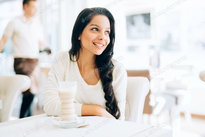 Glamorous lady drinking coffee in a beautiful cafe