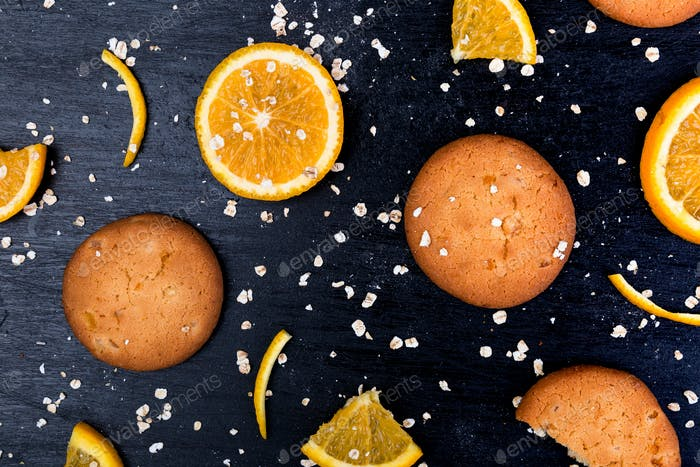 Oatmeal cookies and orange citrus fruit background. Flat lay