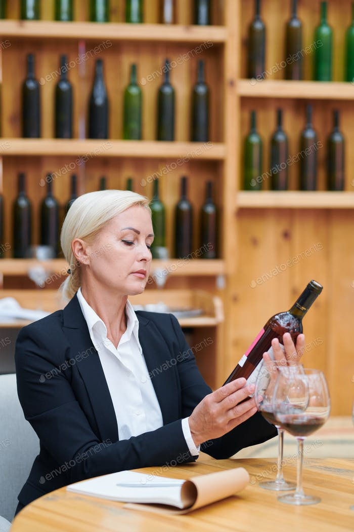 Mature confident winery expert with bottle of wine working in cellar