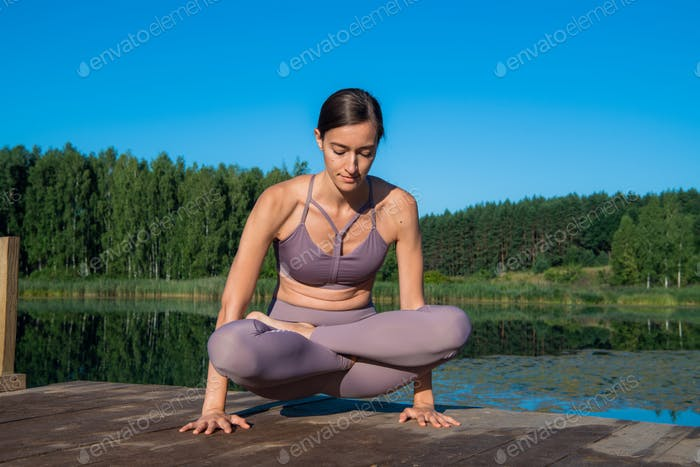 Young attractive girl practices yoga by the lake at sunset. Sitting in lotus position by the water