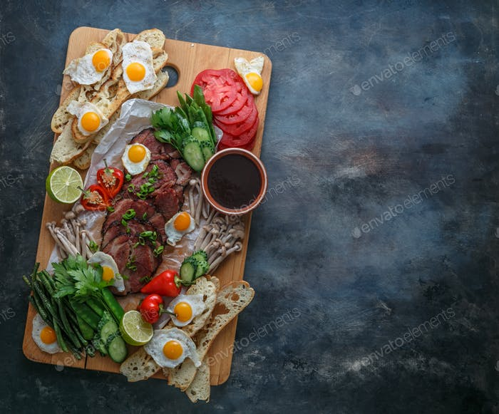 Cutting board with meat, eggs, vegetables, mushrooms, flat lay copy space.
