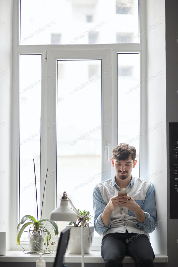 Young stylish man sitting on the window with phone in hands