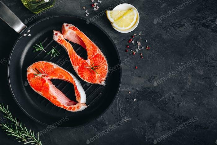 Frische rohe Lachssteaks in Gusseisenpfanne zum Kochen vorbereitet.