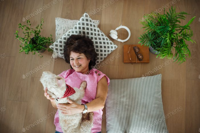 Top view of senior woman with dog lying on floor at home, relaxing