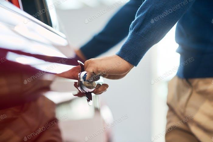 Hand of male businessman opening car door