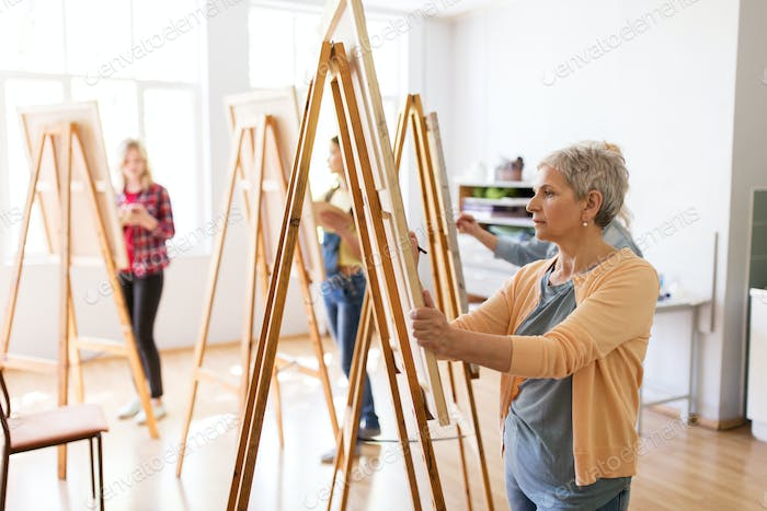 artist with easel and pencil drawing at art school