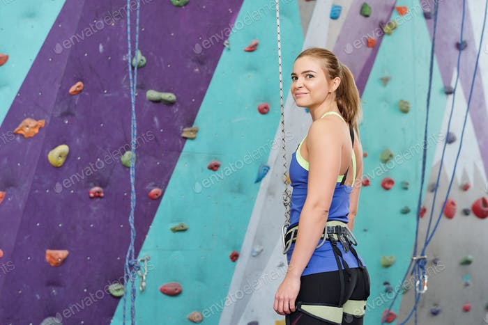 Young blonde woman in special climbing activewear standing by wall