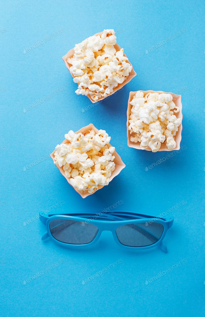 Popcorn with 3d glasses on blue background