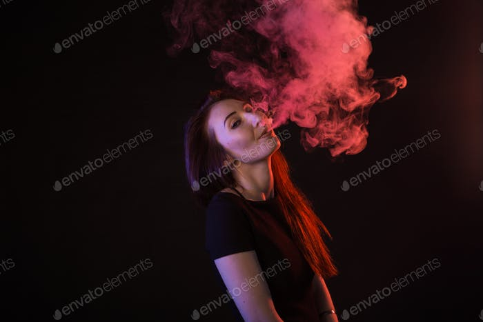 young woman smoking electronic cigarette on dark background