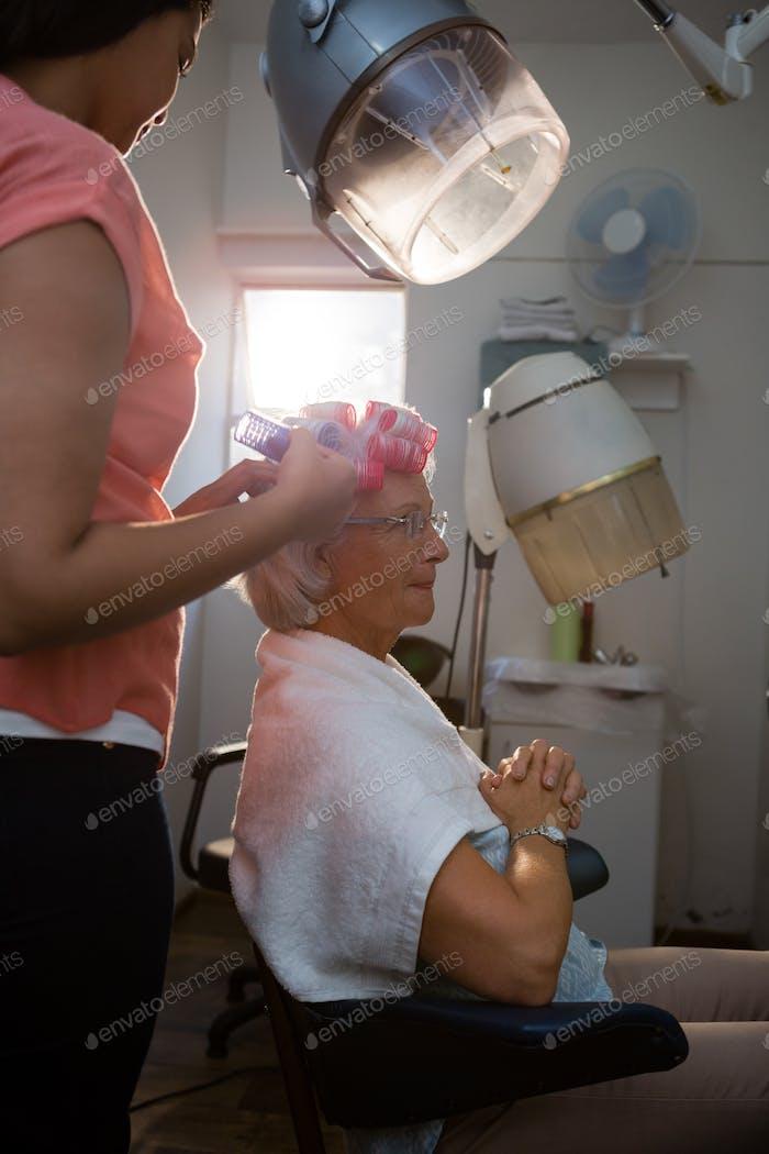 Kosmetikerin Entfernung von Lockenwicklern aus Seniorenhaaren