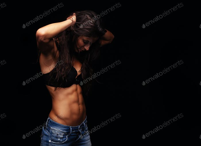 Muscular young woman wearing bra and jeans