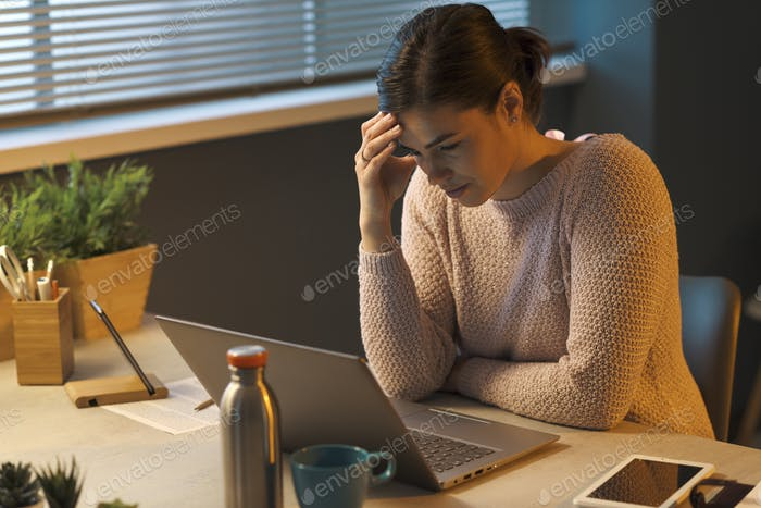 Tired woman with headache working with a laptop