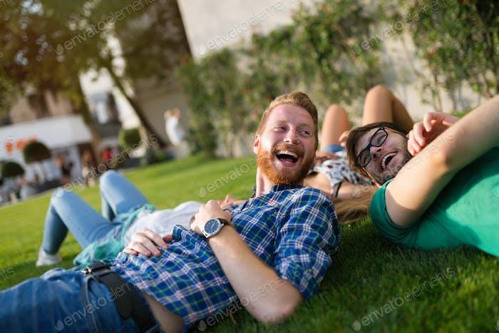 Glückliche Studenten liegen auf dem Boden und lächelnd