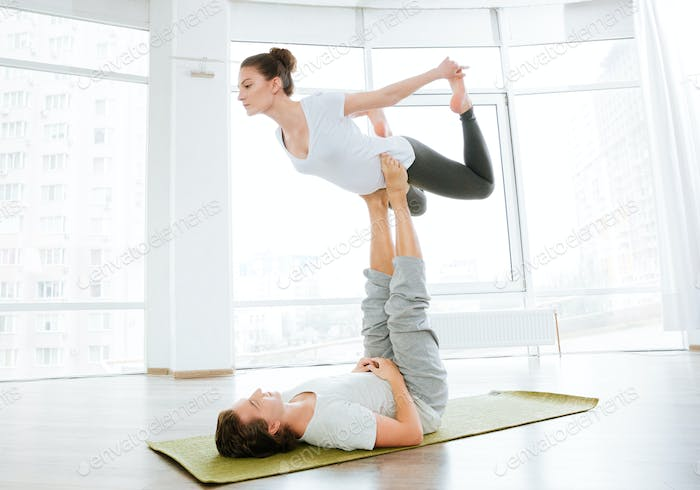 Beautiful couple balancing and doing acro yoga