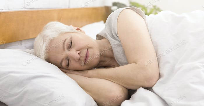 Senior woman sleeping in bed in morning