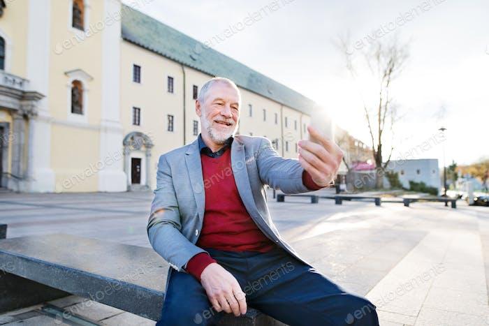 Senior man in town with smart phone, taking selfie.