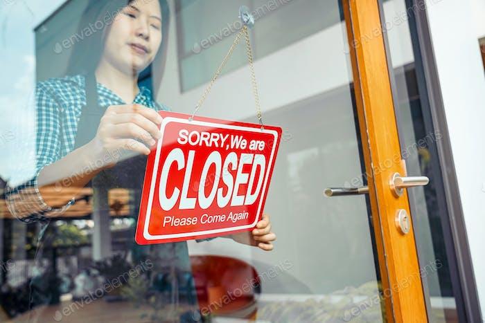 Primer plano de la mano de la mujer joven asiática configuración Cerrar signo en las gafas de la tienda de bienvenida