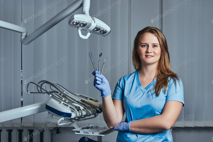 Female dentist holding dental tools while sitting in her dentist office.