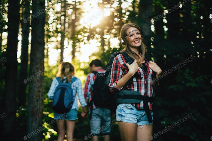 Group of people hiking in forest hand having fun