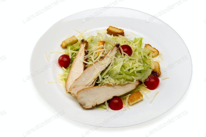 Caesar salad with chicken in a plate on a white background