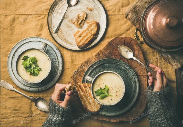 Celery cream soup in cups and female hands in sweater