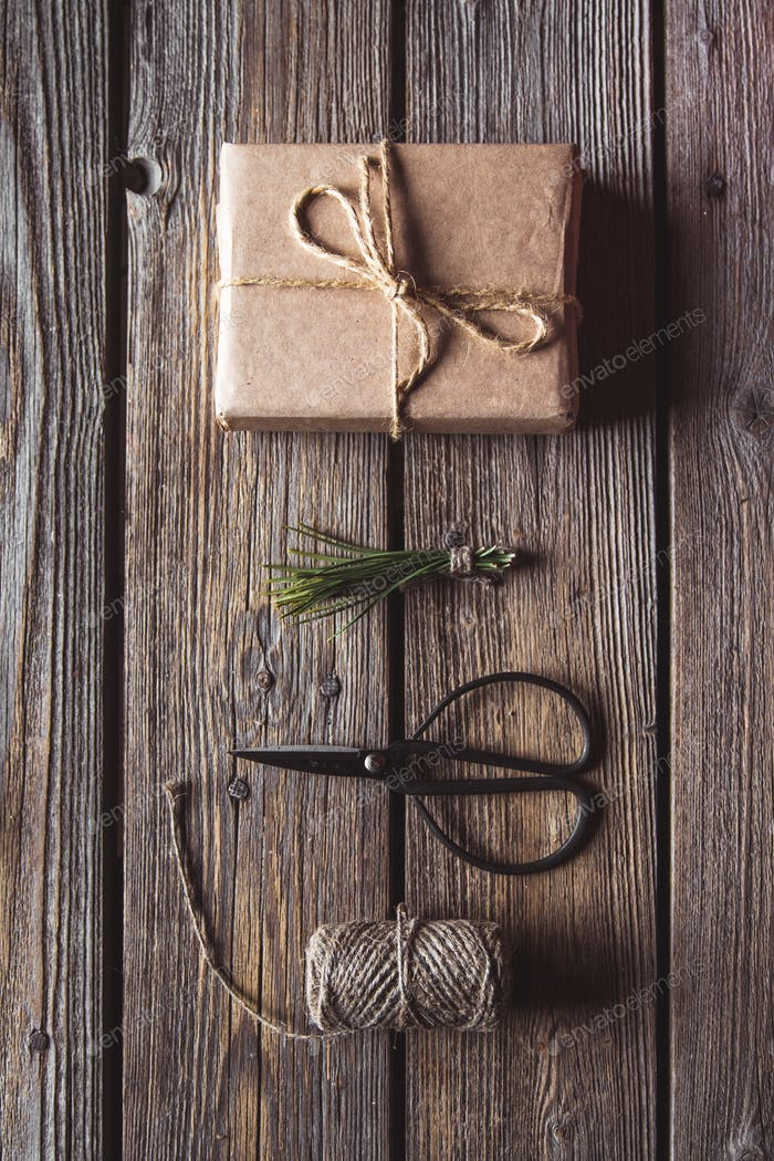 Christmas composition with wrapped presents, pins with decorative cord, scissors and green branches