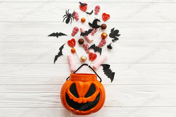 Jack o Lantern bucket with holiday spilling  candy, bats, spiders, skulls