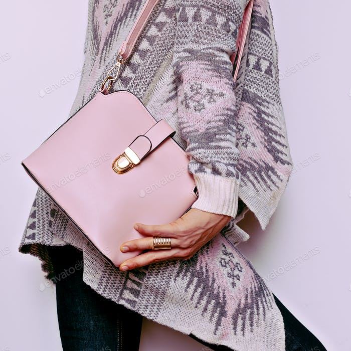 Lady in sweater ornaments and fashion accessories. Bag and styli