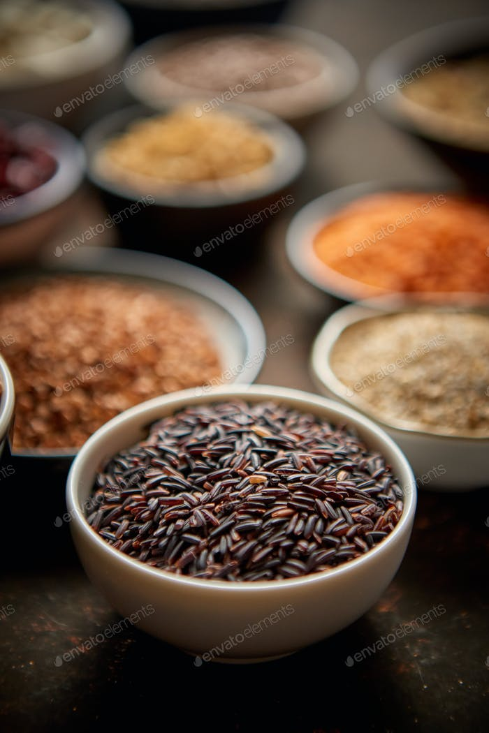 Raw black rice seeds in ceramic bowl. Selective focus