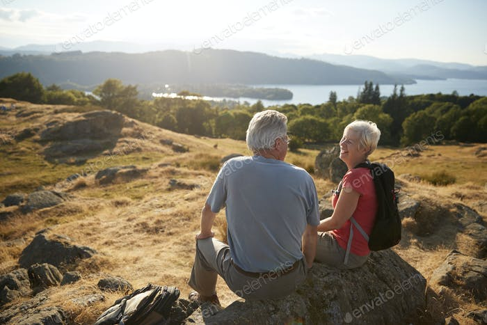 Senior Couple Resting At Top Of Hill On Hike Through Countryside In Lake District UK