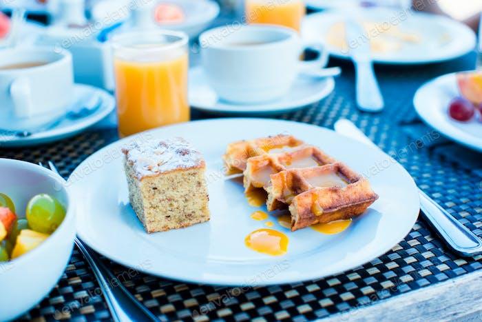 Frischer Obstsalat, Waffeln, Kuchen, Kaffee und Saft zum Frühstück im Resort-Restaurant