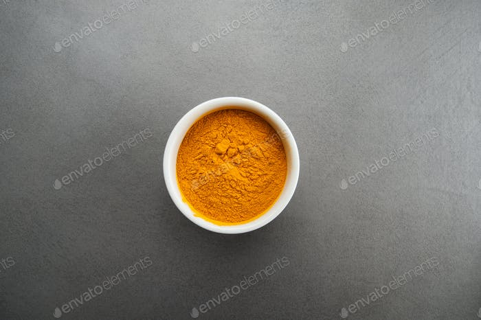 Seasoning curry on a gray textured stone table.