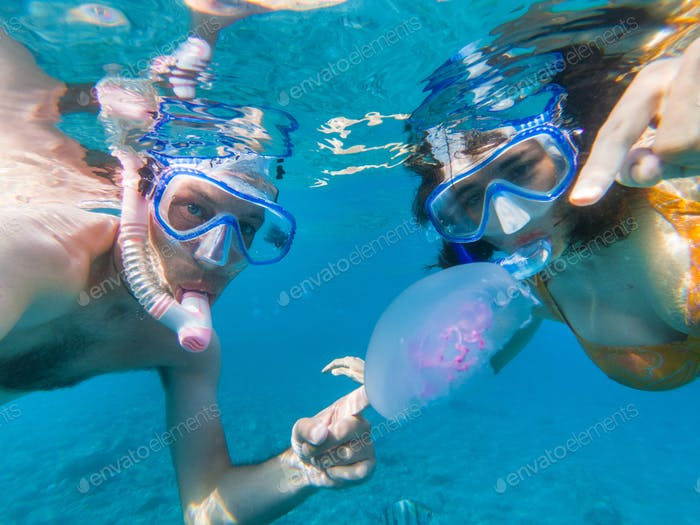 Couple snorkeling underwater with fishes and jellyfishes