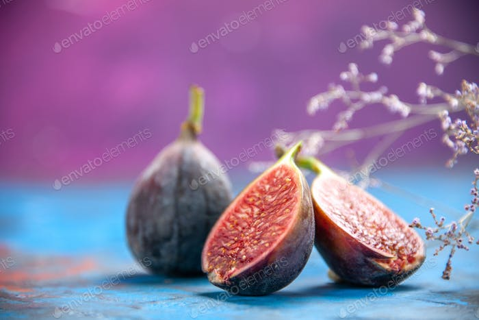 High resolution photo of fresh black mission figs on blue background