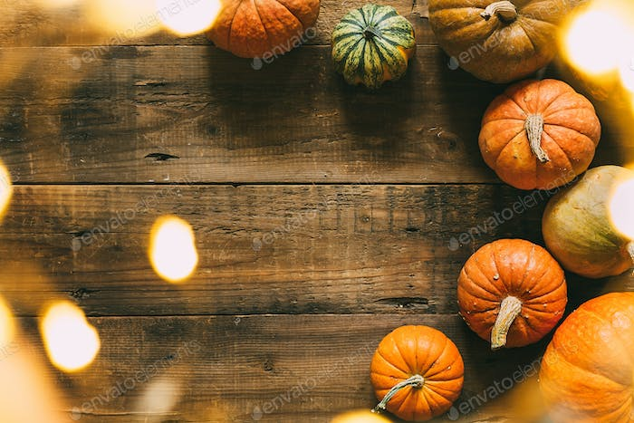 Different pumpkins on a wooden surface with bokeh lights