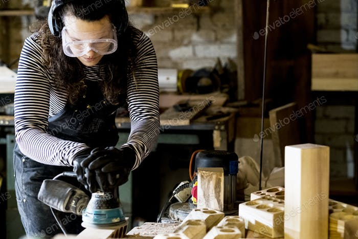 Woman with long brown hair wearing dungarees, safety glasses and ear protectors standing in wood
