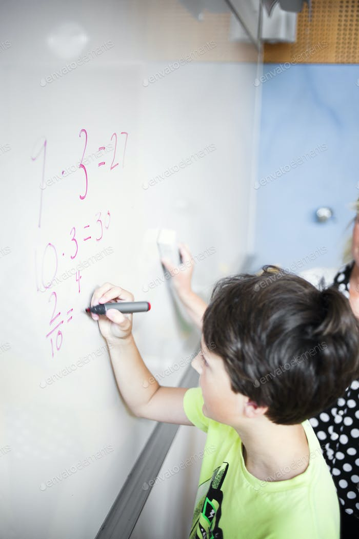 Schoolboy solving mathematics on whiteboard with teacher in classroom