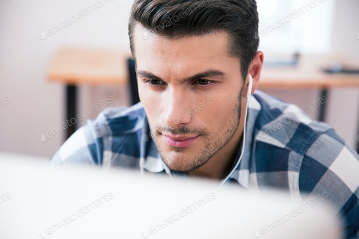 Young businessman with headphones using PC