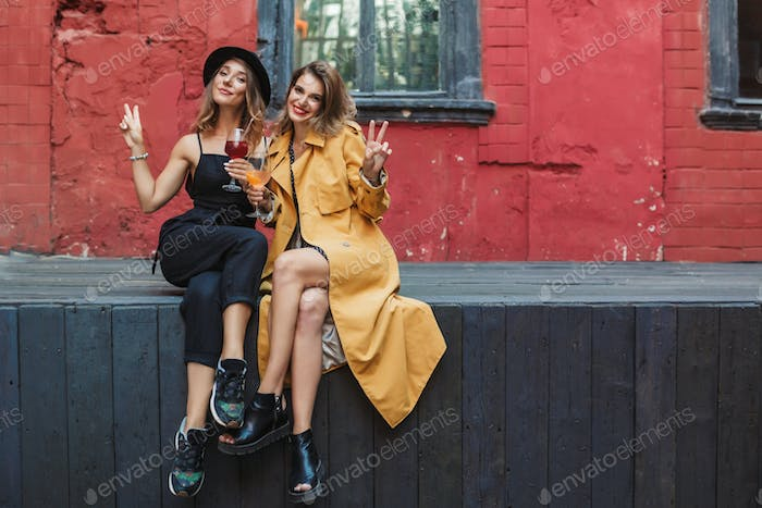 Two young beautiful women with cocktails in hands happily lookin