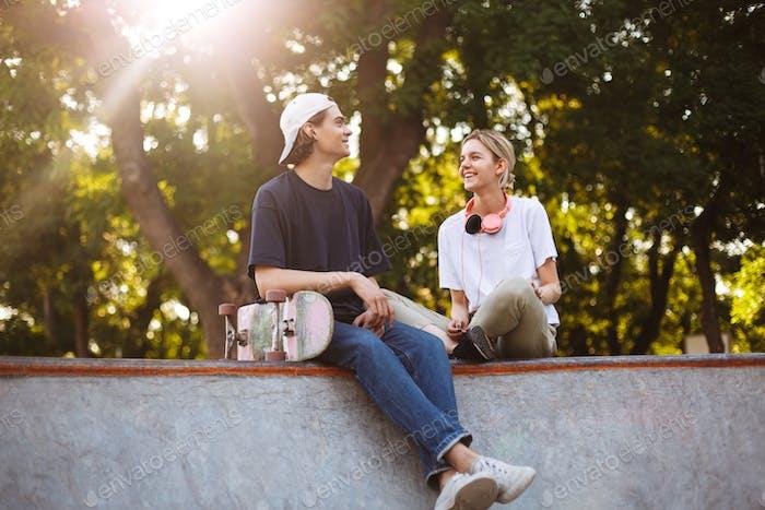 Smiling girl with headphones and young guy with skateboard joyfu
