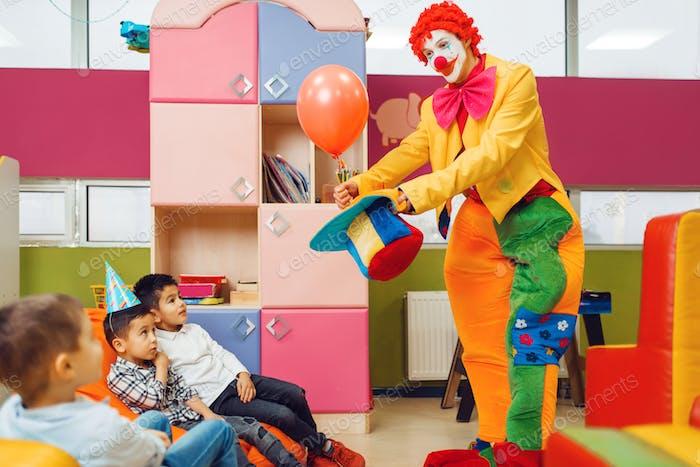 payaso divertido muestra trucos a los niños sorprendidos