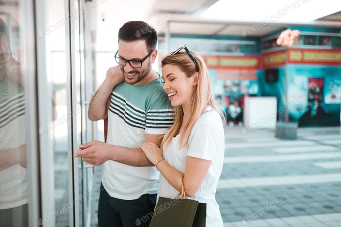 Happy couple is looking at shop window in a shopping mall