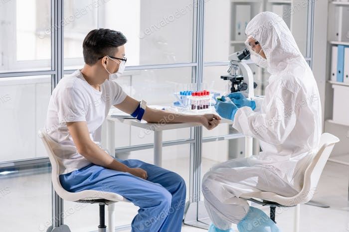 Worker of medical laboratory in protective workwear going to take blood