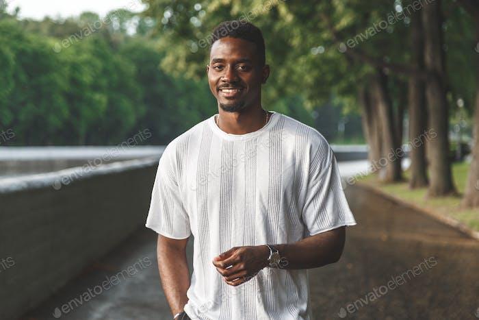 Young man smiling at camera in a park. Horizontally framed shot.