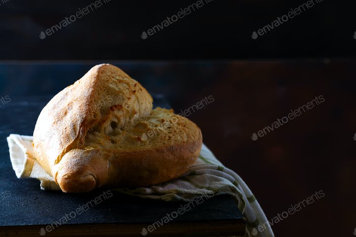 Homemade french bread with a napkin on a dark background, copy space